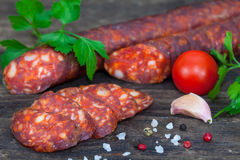 Smoked sausage with tomato. Pepper, garlic and herbs Stock Photos