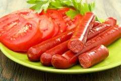 Smoked sausage and tomatoes. Royalty Free Stock Images