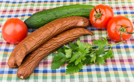Smoked sausage, tomatoes, cucumbers and parsley on tablecloth Stock Photography