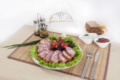 Smoked sausage with tomatoes and lettuce leaves on a plate. royalty free stock photos