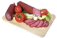 Smoked sausage. With vegetables on the wooden plate stock photos