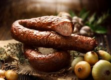 Smoked  sausage on a wooden rustic table with addition of fresh aromatic herbs and spices Royalty Free Stock Image