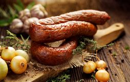 Smoked  sausage on a wooden rustic table with addition of fresh aromatic herbs and spices Stock Photography