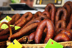 Smoked sausages in baskets with price tags Royalty Free Stock Images