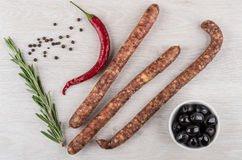 Smoked sausages, chili pepper and twigs of rosemary, black olive Royalty Free Stock Images