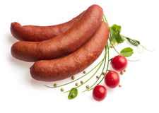 Smoked sausages decorated with tomatoes, onion... Smoked sausages decorated with tomatoes, onion, pepper and leafs of green pea over white background Stock Image