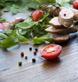 Smoked sausages with greens and cherry tomatoes Stock Images