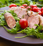 Smoked sausages with greens, cherry tomatoes. Smoked sausages with cherry tomatoes and salad Stock Photos