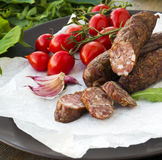 Smoked sausages with greens, cherry tomatoes Royalty Free Stock Photography