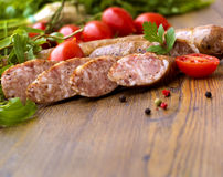Smoked sausages with greens, cherry tomatoes. Smoked sausages with cherry tomatoes and salad Stock Images