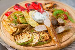 Smoked sausages with grilled tomatoes, paprika, mushrooms, zucchini, fried potatoes, dill, white sour sauce stock photos