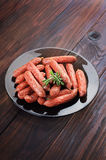 Smoked sausages on plate Royalty Free Stock Photos