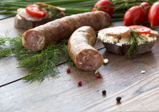 Smoked sausages and sandwiches with greens and cherry tomatoes. Smoked sausages and sandwiches with greens and  tomatoes Stock Image
