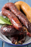 Smoked sausages on white dish Royalty Free Stock Image