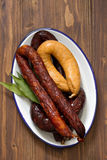 Smoked sausages on white dish Stock Photo