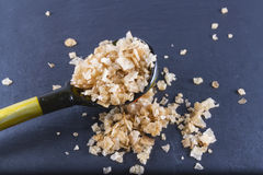 Smoked sea salt flakes, on a wooden spoon and scattered. Macro. Royalty Free Stock Images