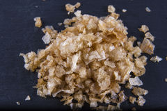 Smoked sea salt flakes, on a wooden spoon and scattered. Macro. Royalty Free Stock Image