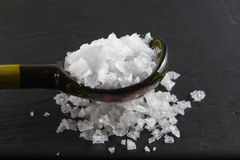 Sea salt flakes, on a wooden spoon and scattered.  Stock Image