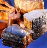 Smoked sliced salt fish. Smoked sliced salt different fish on blue mirror background Stock Image