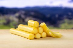 Smoked slovak string cheese stick with alps behind stock image