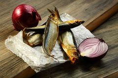 Smoked sprat and red onion. Royalty Free Stock Photo