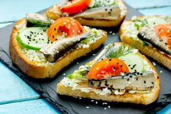 Smoked sprat sandwich - fish, boiled egg, fresh cucumber. And tomato, black and white sesame, dill sandwiches on fried bread slices royalty free stock images