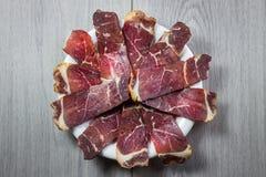 Smoked torkade kött på den vita plattan arkivfoton