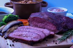 Smoked Tri Tip Roast with all the fixins. A Slow and low smoked Tri Tip Roast with sides of vegetables, and baked beans royalty free stock images