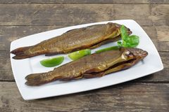 Smoked trout with basil. And lemon on white plate Royalty Free Stock Photos