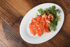Smoked trout with greens. On a white plate. Wooden background Stock Photos