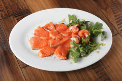 Smoked trout with greens. On a white plate. Wooden background Stock Photography