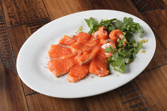 Smoked trout with greens. On a white plate. Wooden background Stock Photo