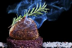 Smoked veal loin with sesame and rosemary on a bed of salt and dark background stock photography