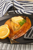 Smoked warm scottish kipper with butter. In a pan Stock Images