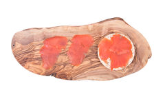 Smoked wild pacific sockeye salmon. On organic brown rice cake and olive wood cutting board isolated on white background Royalty Free Stock Image