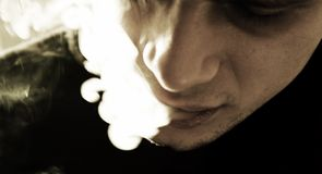 Smoker. Closeup of a man's face with cigarette smoke coming out of his mouth stock image