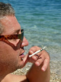 Smoker on beach Royalty Free Stock Photo