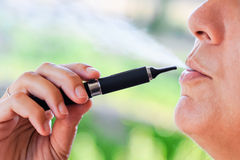 Smoker of Electronic Cigarette with steam Royalty Free Stock Images
