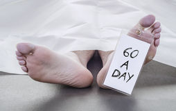 Smoker. Feet of a deceased man under white blanket with a toe tag that reads 60 a day Stock Photos