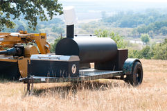 Smoker grill on a farm. Smoker grill on a camo trailer out on a farm with a scenic view in background Royalty Free Stock Images