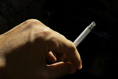 Smoker hand. The hand hold a cigarette with dark background royalty free stock image