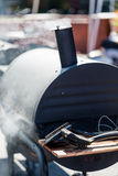 Smoker. Large barbecue smoker cooking meat stock photography
