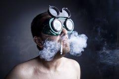 Smoker Man. Portrait of crazy smoker man in studio Royalty Free Stock Image