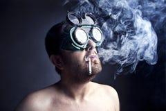 Smoker Man. Portrait of crazy smoker man in studio Stock Image