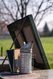 Beekeeping equipment. A smoker placed on a beehive in apiary. Ready to calm the bees royalty free stock images