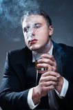 Smoker in suit with cigarette and glass of whiskey Royalty Free Stock Photo