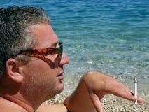 Smoker with sunglasses on beach Royalty Free Stock Image