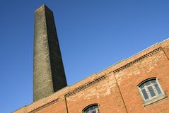 Smokestack. A disused smokestack towers above an old industrial building royalty free stock photos