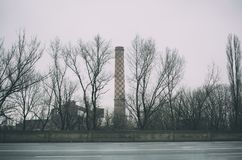 Smokestack and bare tree. Smokestack and chimney in the factory. Bare broad-leaved trees in the foreground. Heavy overcast Stock Photos