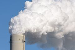 A smokestack of a coal power plant. Close up of a smokestack of a fossil fuel coal power plant with white smoke against a completely blue sky and lots of copy Royalty Free Stock Photo
